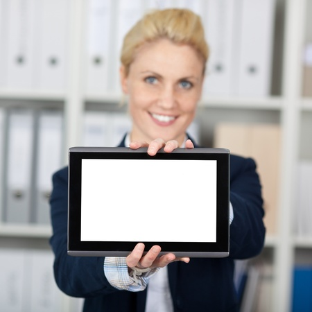 Portrait of a smiling young businesswoman presenting digital tablet in the office photo