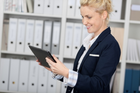 Smiling young businesswoman using tablet pc in the office photo