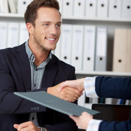 contratos: Sonriente hombre de negocios dando la mano a una entrevistadora mujer recortada en la oficina