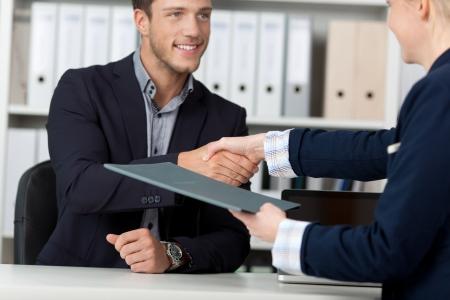 entrevista de trabajo: Feliz hombre de negocios dando la mano a un entrevistador de la mujer en la oficina