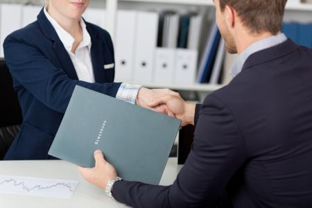 Buik van een zakenman handen schudden met een vrouwelijke interviewer in kantoor