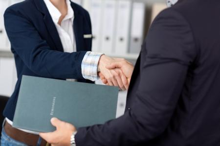 entrevista de trabajo: Sección media de un hombre de negocios dando la mano a una entrevistadora mujer recortada en la oficina Foto de archivo