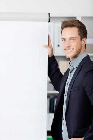 Portrait of a young smiling businessman with flipchart photo
