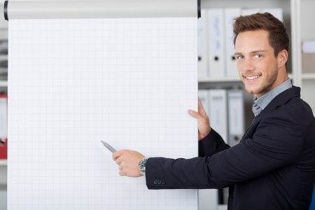 whiteboard: Portrait of a young businessman showing free text space on flipchart