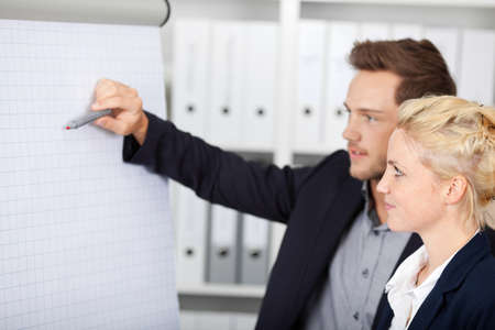 Side view of two young businesspeople working on flipchart at office photo