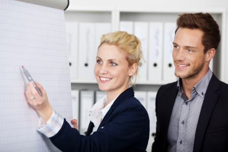 formals: Side view of two young businesspeople working on flipchart at office Stock Photo