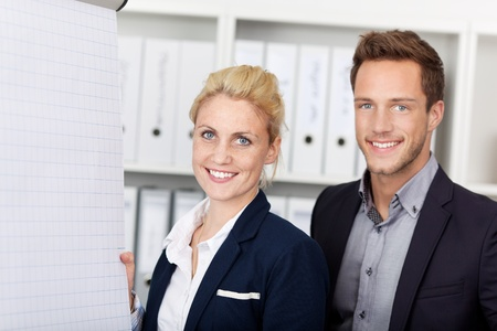 Side view of two young smiling businesspeople working on flipchart at office Stock Photo