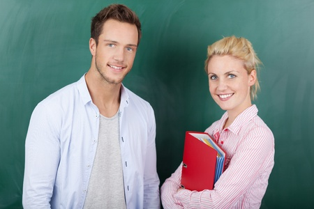 Portrait of a smart young man and woman with folder standing against green background photo