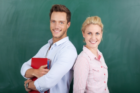 Portrait of a smiling young man and woman holding folder in front of chalkboard photo