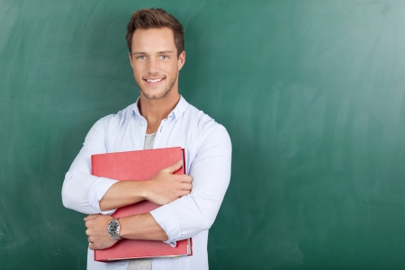 Portrait of a smart young man with binder standing against chalkboard 版權商用圖片 - 21149579