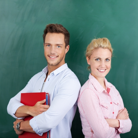 Portrait of a smart young man and woman with binder standing against chalkboard photo