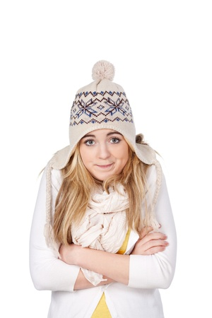 Image of a cute female teen shivering due to cold despite of wearing lots of warm clothes, isolated on white background. photo