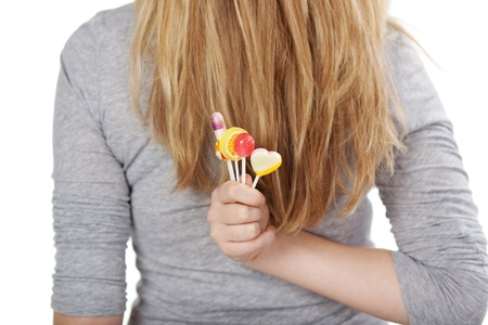 overweight students: Photograph of a female hiding her lollipops behind the back, isolated on white background. Stock Photo