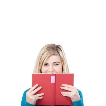 Portrait of a teenage girl looking over book against white background photo