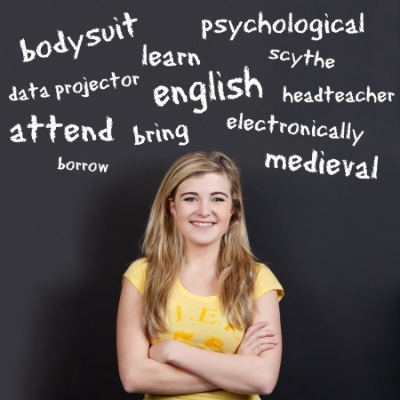 vocabulary: Portrait of a confident smiling teenage girl with arms crossed against English vocabulary on black background