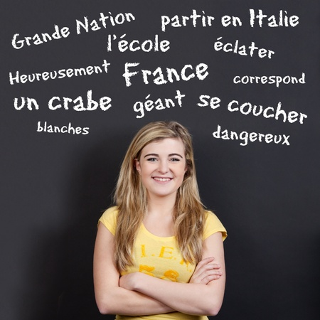 vocabulary: Portrait of a confident smiling teenage girl with arms crossed against French vocabulary on black background