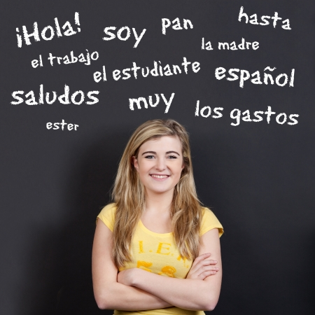 foreign: Portrait of a confident smiling teenage girl with arms crossed against Spanish vocabulary on black background