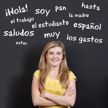 języki: Portret pewność uśmiechnięta nastolatka z rękami skrzyżowanymi przed hiszpańskiego słownictwa na czarnym tle Zdjęcie Seryjne