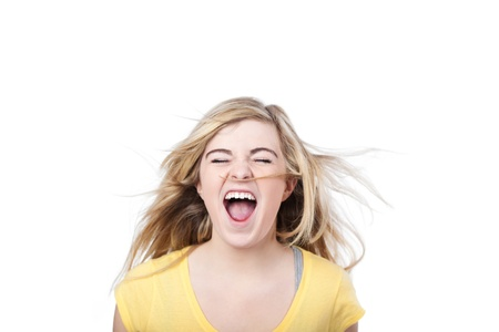 madly: Photograph of a young female shouting madly, isolated on white background. Stock Photo