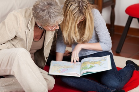 Photograph of a teenage girl with her grandmother looking at maps of the world. photo