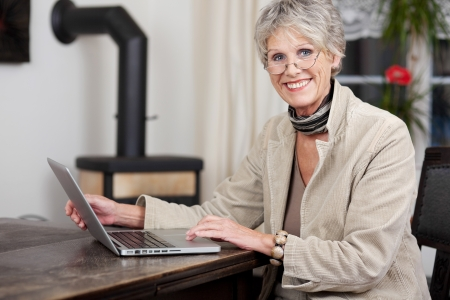Side profile of a senior female smiling while working on her\ laptop.