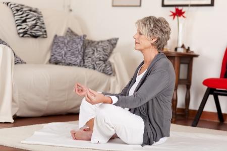 Photograph of a senior female doing yoga in her living room.