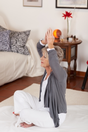 tai chi: Photograph of a senior female raising her folded hands above head, while doing yoga practice in her living room.