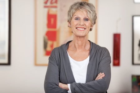 Portrait of a confident smiling senior woman standing with arms crossed at home photo