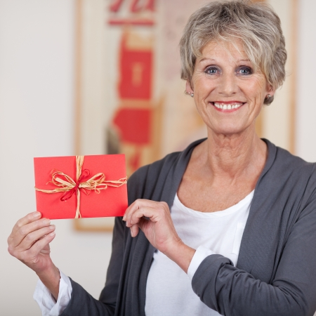 Image of a smiling elderly woman showing a decorated envelope. photo