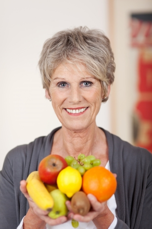 senior eating: Portrait of a smiling senior woman holding a variety of fruits in her hands Stock Photo