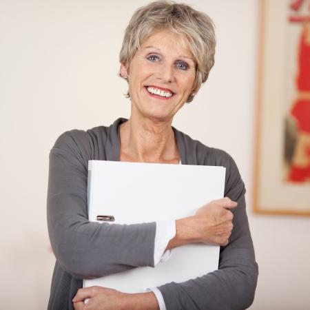 1 senior: Retrato de una mujer mayor sonriente que sostiene la carpeta blanca Foto de archivo