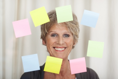 positive thinking: Portrait of a smiling senior woman with sticky notes against blurred background