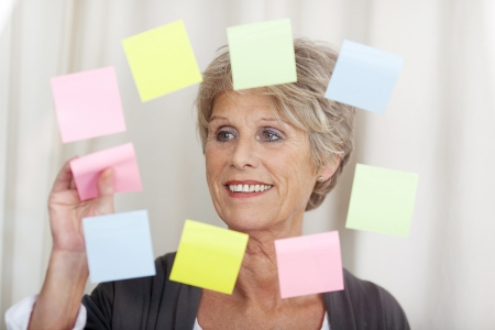 Image of a senior woman removing sticky notes. photo