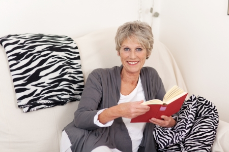 Portrait of a smiling senior woman with book sitting on sofa photo
