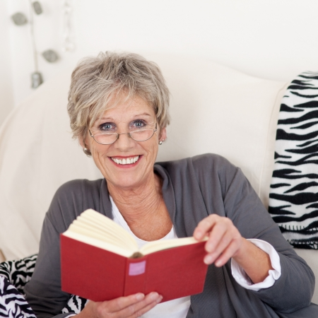 Portrait of a smiling elderly female reading a book and giving a beautiful smile. photo