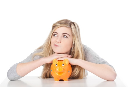 thoughtful woman: Image of a cute teenage girl posing with piggy bank.
