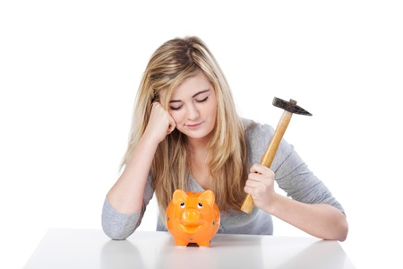 Displeased teenage girl with piggy bank and hammer against white background photo