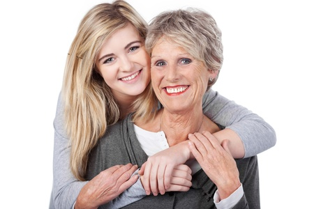 Portrait of a happy teenage girl embracing grandmother from behind against white background photo