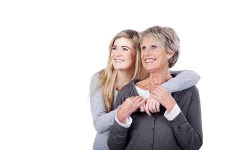 Image of a modern grandma posing with her granddaughter, both looking at something and smiling.