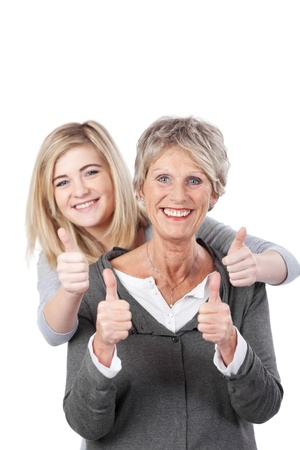 kinship: Portrait of grandmother and granddaughter showing thumbs up against white background