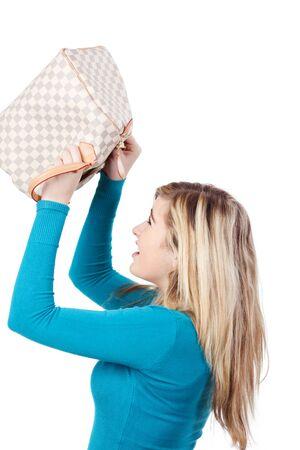 beroofd: Zijaanzicht van een tiener blond meisje op zoek naar lege handtas tegen een witte achtergrond
