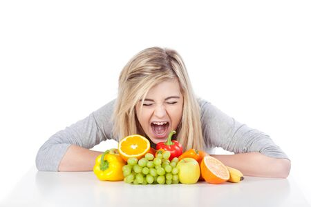 frustration girl: Angry teenage girl screaming out loud in front of fruits against white background