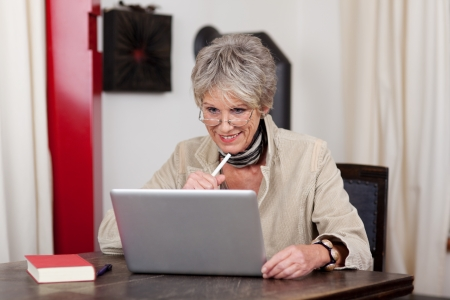 Photograph of smiling senior female using modern technology, working on laptop. photo