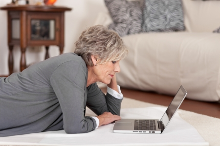 Side view of a female pensioner using laptop in living room at home photo