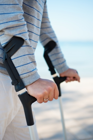 recuperating: Injured Man standing with Crutches on the beach Stock Photo