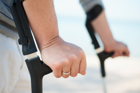 personas discapacitadas: Hombre da�ado Tratar de caminar en las muletas en una playa Foto de archivo