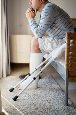 Verletzter Mann in tiefe Gedanken mit einem Bein Gips