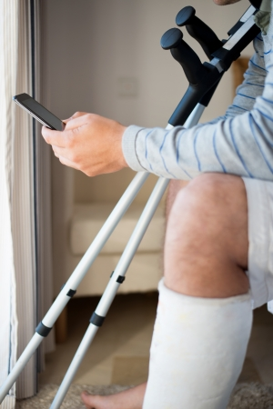 crutches: Young Man with Injury dialing the phone