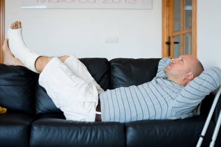 Injured Man Lying on Sofa with leg plaster photo