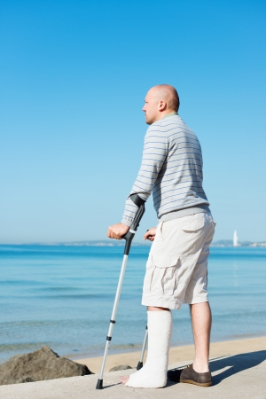 plaster foot: Injured Man with Crutches standing still at sea side Stock Photo